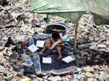 Un niño espera a que sus padres terminen de recoger material reciclable en un basurero de Indonesia