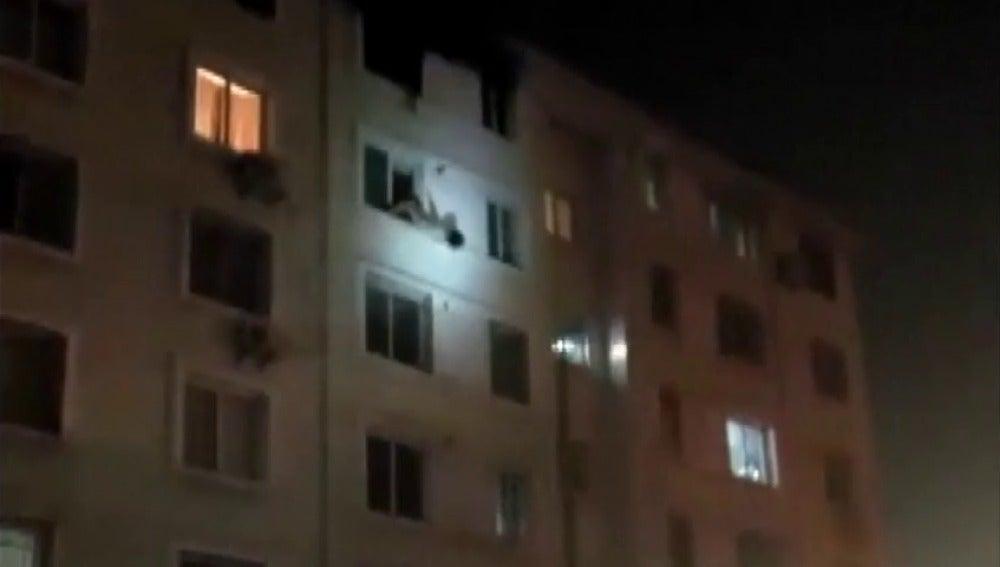 Frame 15.960998 de: Un bombero rescata en el aire a una mujer que cayó al vacío huyendo del incendio de su casa