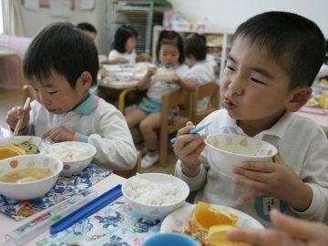 Dos niños disfrutan de su almuerzo en el comedor escolar