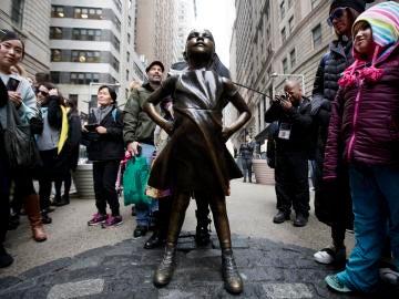 Varias personas observan la estatua en Wall Street de la 'Niña sin miedo'