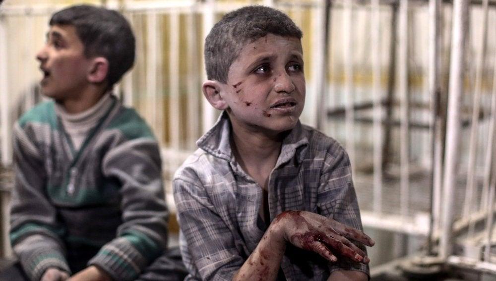 Niños heridos reciben tratamiento médico junto a un charco de sangre