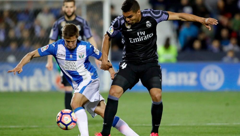 El centrocampista brasileño del Real Madrid, Carlos Henrique Casemiro, disputa un balón con el jugador argentino del Leganés, Alexander Szymanowski