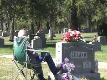 Fred Gilland frente a la tumba de su esposa