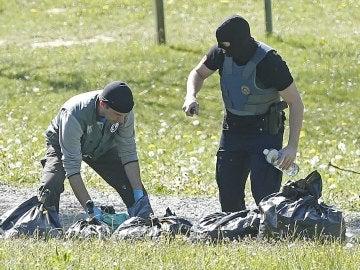 La policía francesa observa las armas encontradas en uno de los zulos cuya localización ha sido facilitada por ETA en la localidad de Saint Pee sur Nivelle, al sur de Francia