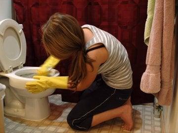 Mujer limpiando el inodoro
