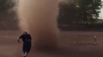 Frame 55.604209 de: Un hombre atraviesa un tornado que apareció en el entrenamiento de fútbol de un grupo de jóvenes