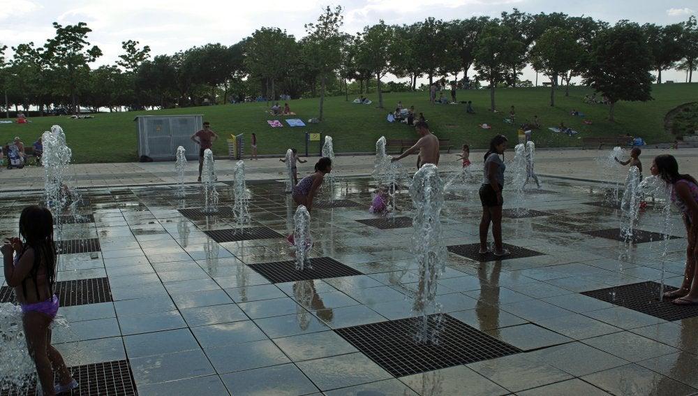 Niños jugando con agua en una fuente