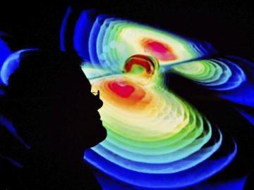 Un científico observa una representación de las ondas gravitacionales