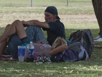 Una pareja se protegen del sol bajo un árbol en Tucson