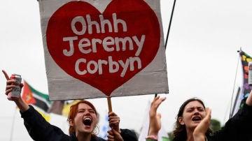 """Una asistente del Festival sostiene una pancarta que hace referencia al cántico de """"Oh Jeremy Corbyn""""."""