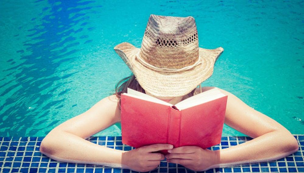 Chica leyendo en la piscina