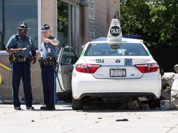 Policías junto al taxi protagonista de los atropellos en Boston