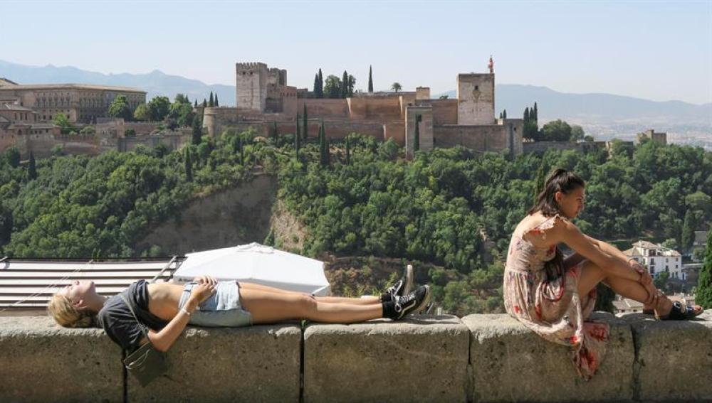 Unos turistas descansan y toman el sol en Granada