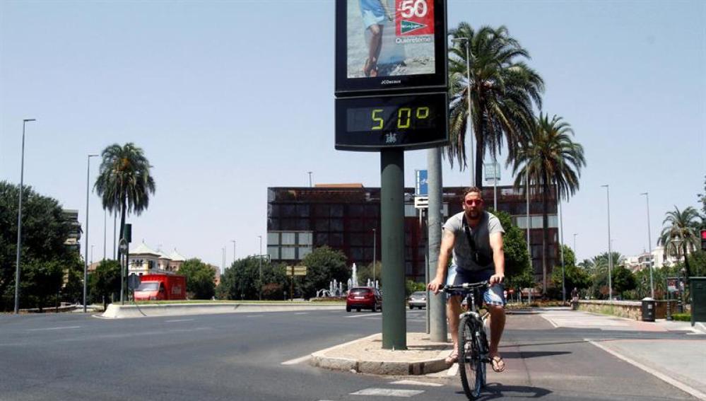 Un joven pasa con su bicicleta junto a un termómetro que marca 50 grados en una calle de Córdoba
