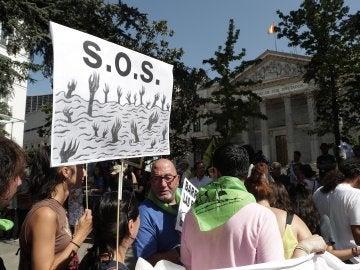 Miembros de unos 100 colectivos por los derechos de las personas migrantes durante la concentración que han protagonizado hoy ante el Congreso para despedir a la Caravana Abriendo Fronteras