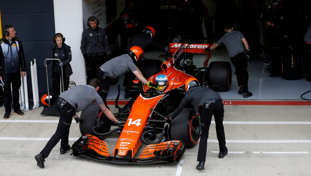 Fernando Alonso mete su coche en el box con la ayuda de sus mecánicos