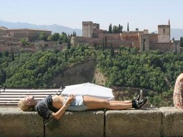 Unos turistas descansan y toman el sol en Granada.