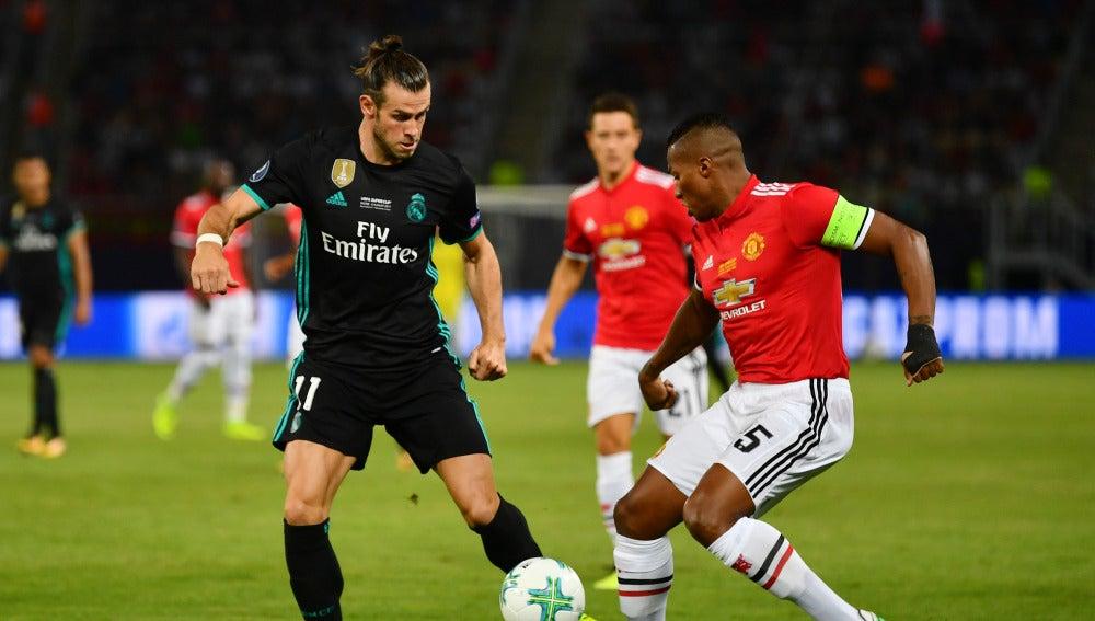Gareth Bale pelea un balón con Antonio Valencia