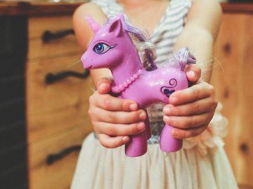 Una niña sostiene con sus manos un unicornio de juguete