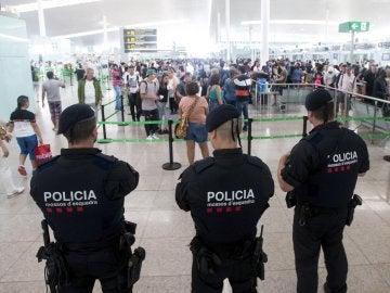 Agentes de los Mossos d'Esquadra controlan de los accesos a las puertas de embarque en el Aeropuerto de El Prat