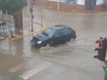 Un coche atravesando una calle de humilladero tras la tormenta