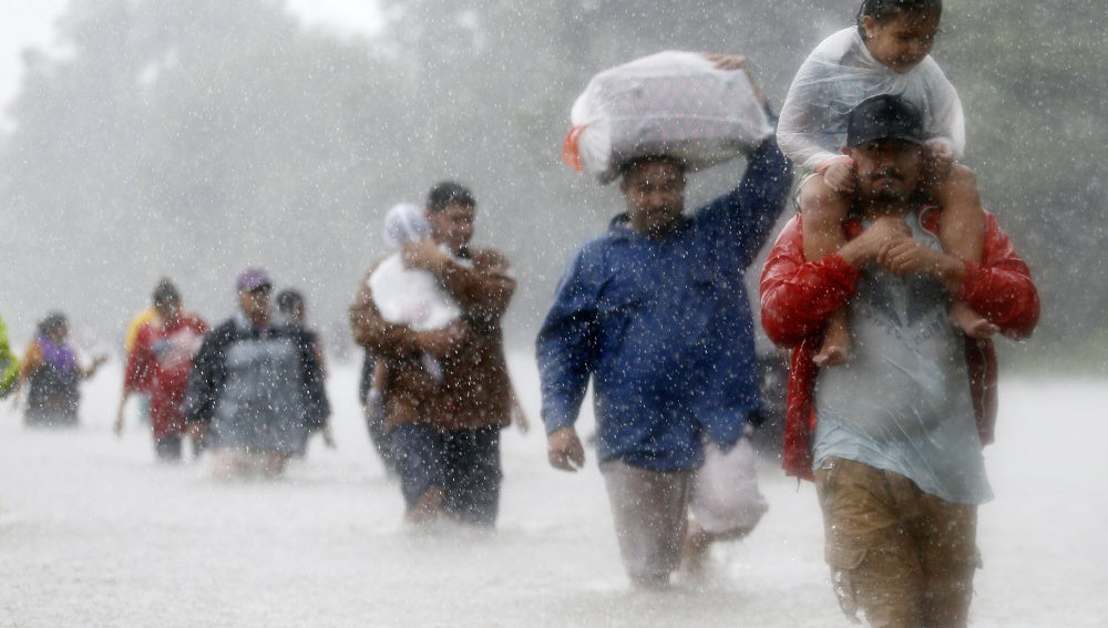 Los residentes caminan por zonas inundadas que deja la tormenta tropical Harvey en Beaumont Place, Houston