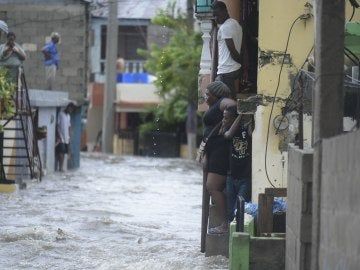 Personas observan una calle inundada en República Dominicana