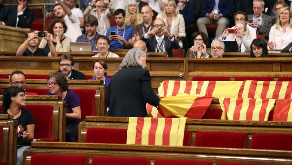 Àngels Martínez retirando las banderas de España en el Parlament