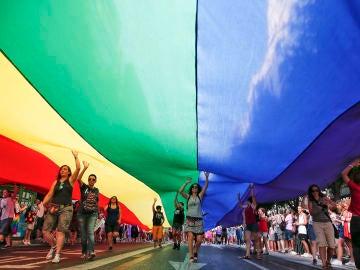 Varias personas portan una bandera arcoriris gigante