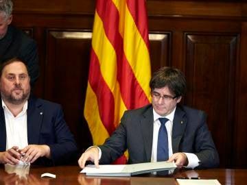 El presidente de la Generalitat, Carles Puigdemont, acompañado por el vicepresidente Oriol Junqueras, firma la convocatoria de referéndum en el Parlament