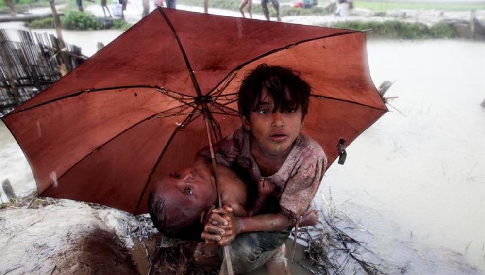Dos niños rohinyás se refugian de la lluvia