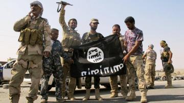 Unos soldados de Daesh exhiben su bandera