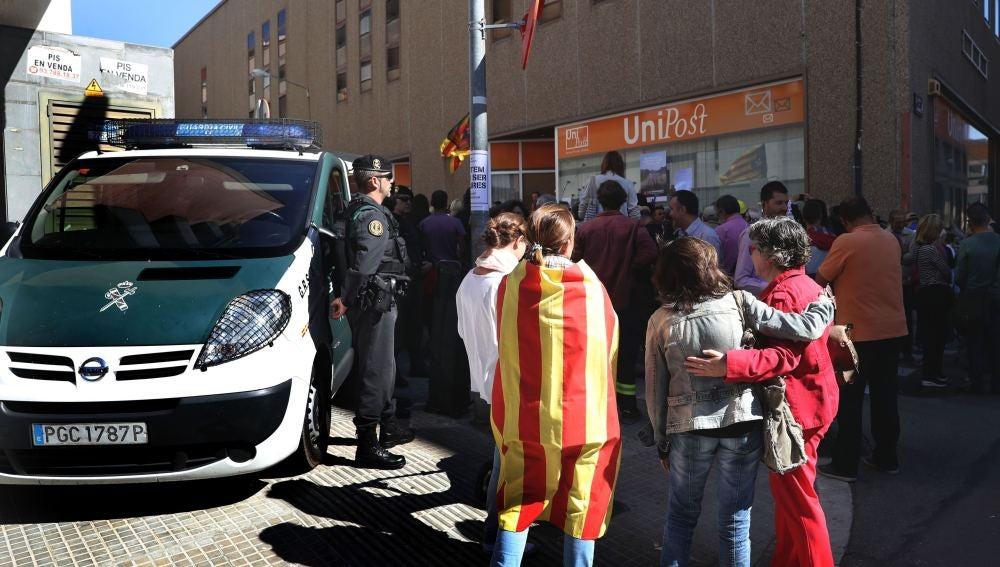 Numerosas personas permanecen ante la oficina de la empresa de mensajería Unipost en Terrassa
