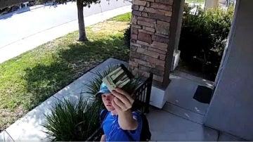 El joven muestra a la cámara de seguridad la cartera encontrada