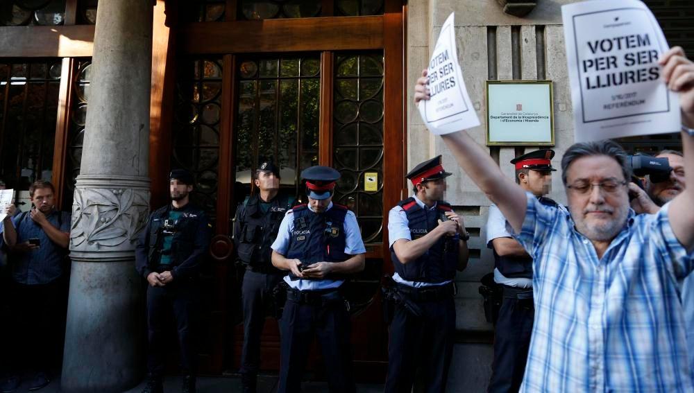 Agentes de la Guardia Civil y de los Mossos d'Esquadra, en la puerta de la consellería de Economía de la Generalitat