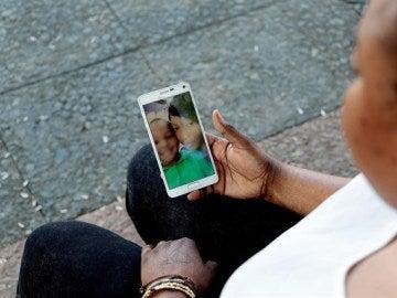 Oumo viendo imágenes de su hijo en el móvil