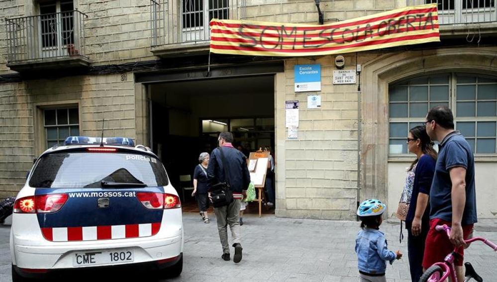 n vehiculo de los Mossos d'Esquadra a la entrada del colegio público Cervantes que permanece abierto