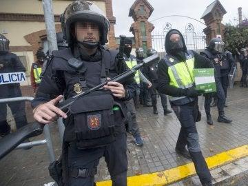 Agentes antidisturbios de la Policía Nacional retiran material