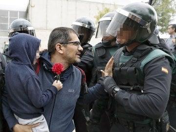 Un padre con su hijo en brazo conversa con un guardia civil ante uno de los colegios