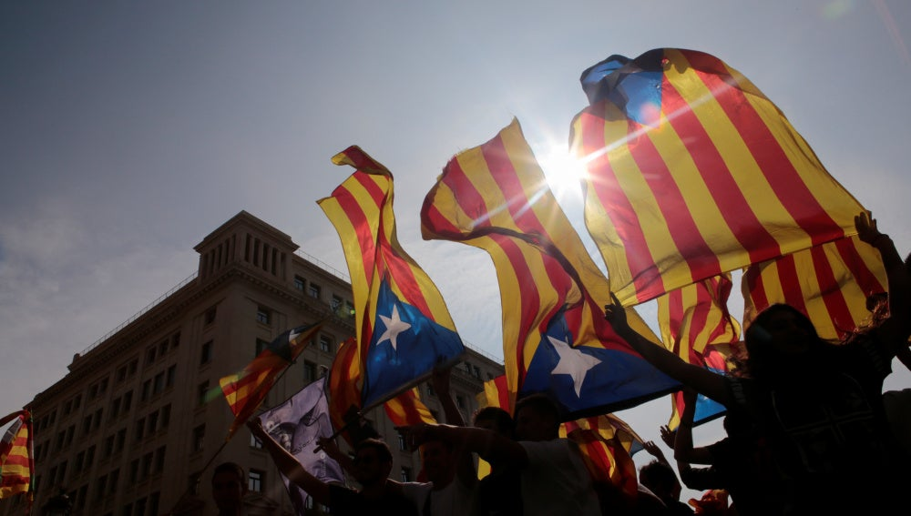 Manifestantes sostienen banderas esteladas durante la huelga del 3-O
