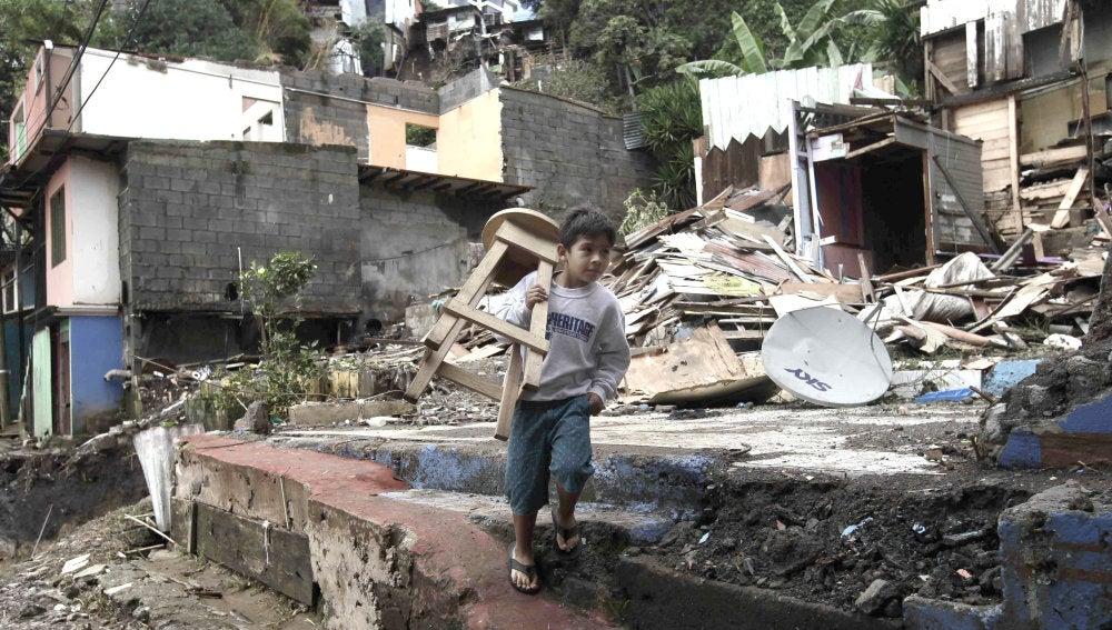 Un niño carga una silla en medio de los escombros en el cantón de Escazú