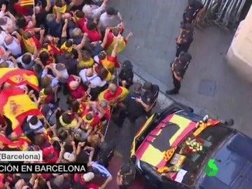 Un grupo de manifestantes entrega flores y banderas de España a los agentes de la Policía Nacional