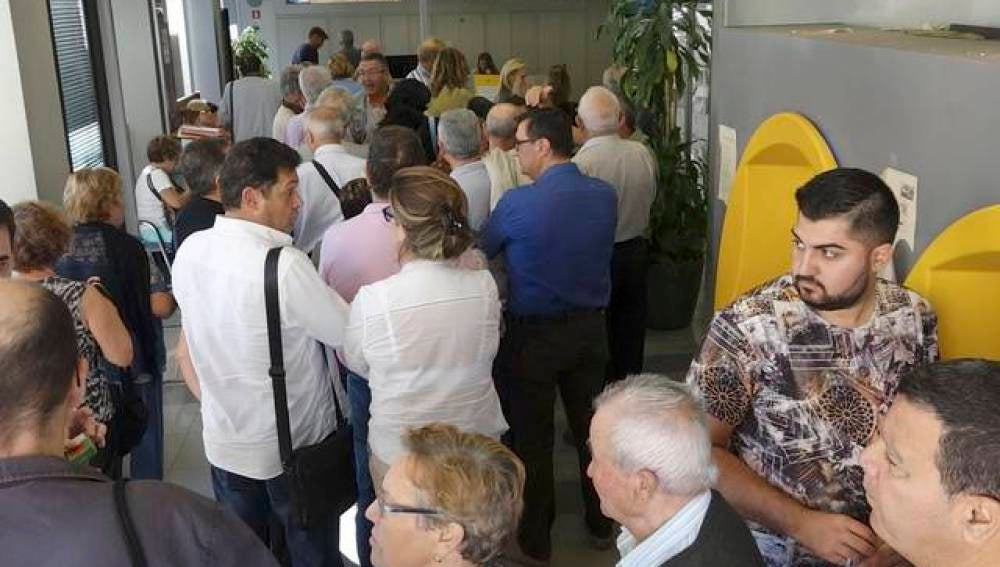 Personas haciendo cola en una sucursal bancaria de Fraga