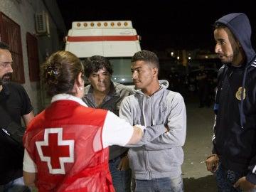 Miembros de la Cruz Roja atienden a un grupo de inmigrantes que viajaba a bordo de una de las pateras rescatadas