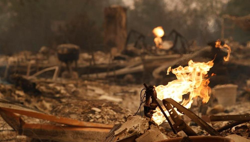 Vista del fuego saliendo de una pipa de gas de una casa quemada en California