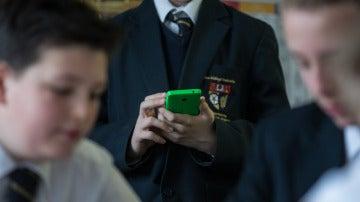 Un alumno con un móvil en el colegio