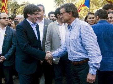 El presidente de la Generalitat, Carles Puigdemont, saluda a Artur Mas