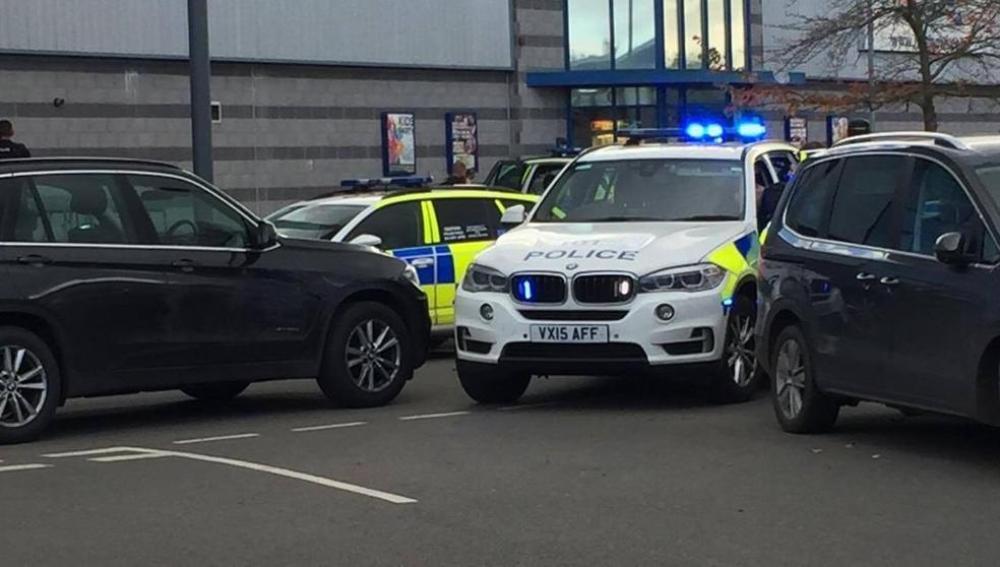 Imagen de una patrulla de la policía británica frente al parque de ocio de Nuneaton, donde habría un hombre armado con rehenes en una bolera