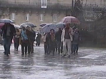 Gente paseando en Santiago de Compostela lloviendo