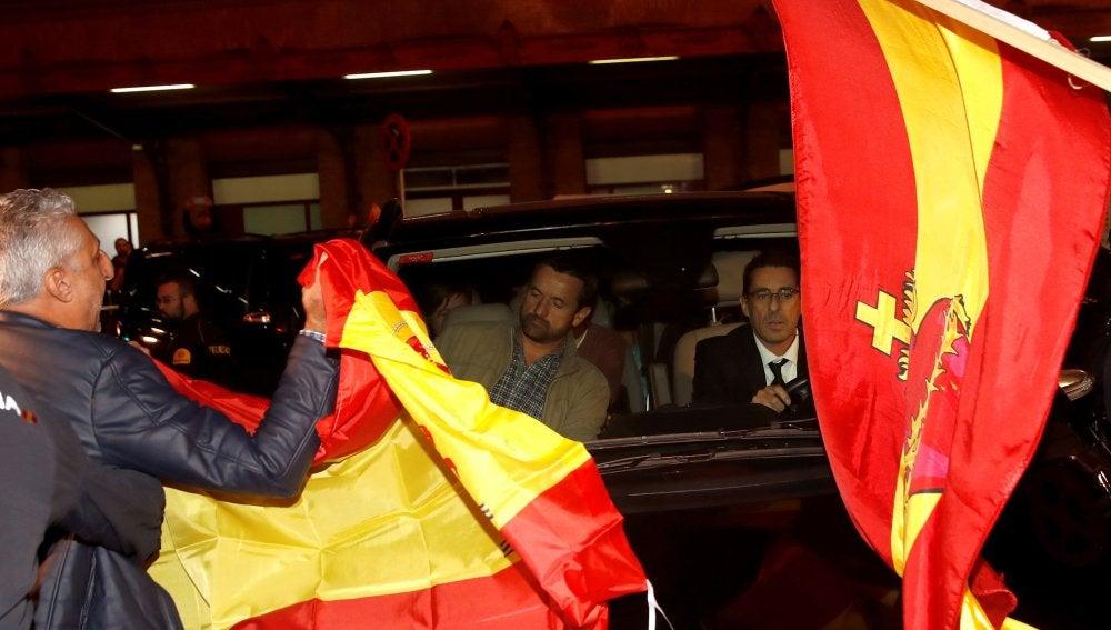 Un grupo de personas con banderas españolas rodean el coche de los miembros de la mesa del Parlament